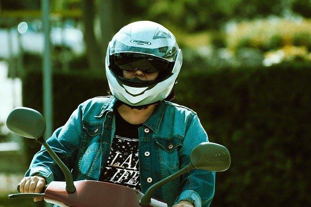 muž v helmě řídící skútr